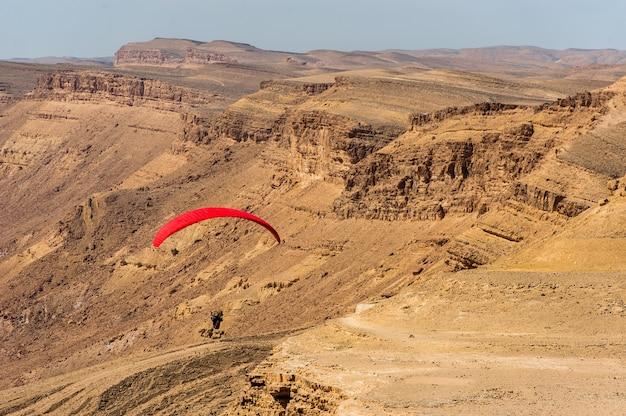 Un parapente survole le désert israélien.