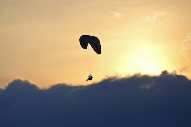 Parapente volant sur une aile dans le ciel contre le soleil couchant