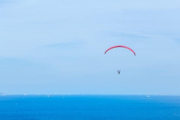 Parapente volant à travers la mer et le beau ciel, koh lan pattaya thaïlande