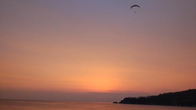 Un parapente vole sur fond de coucher de soleil