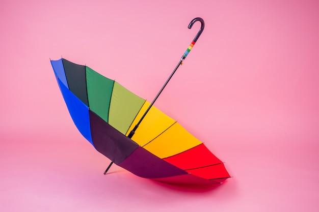 Parapluie arc-en-ciel coloré sur fond rose en studio