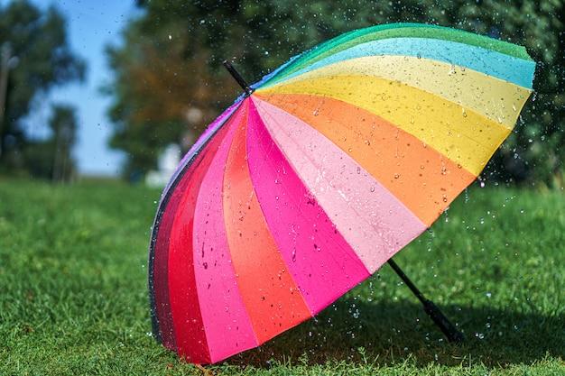 Parapluie arc-en-ciel de couleur vive sur l'herbe pendant la pluie d'été
