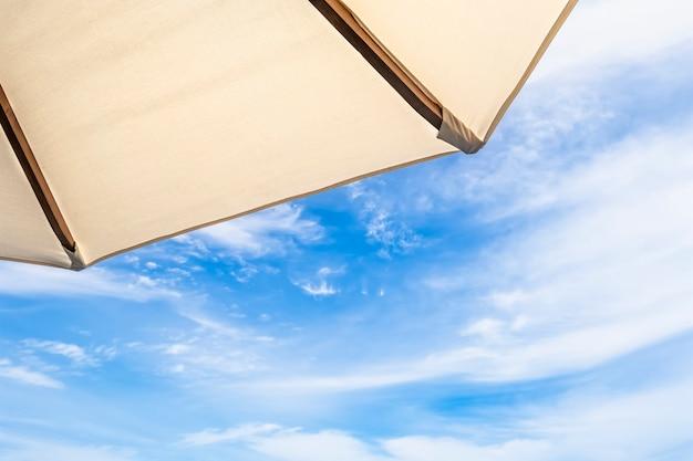 Parapluie blanc sur ciel bleu avec des nuages