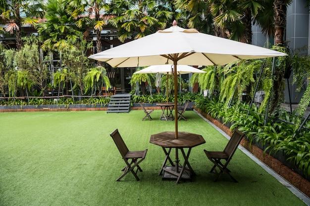 Parapluie blanc dans des chaises et un magnifique jardin dans un complexe extérieur et un hôtel.