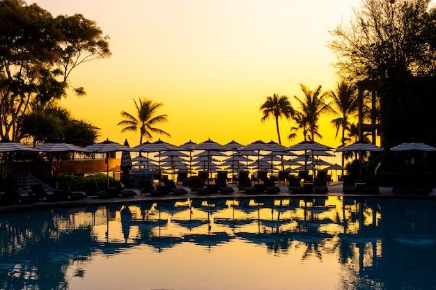 Parapluie et canapé chaise autour de la piscine extérieure de l'hôtel pour les vacances de voyage