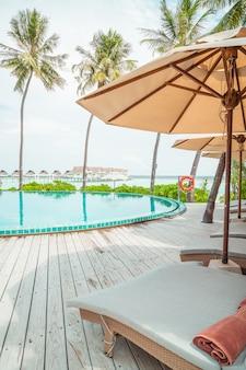 Parapluie et chaise autour de la piscine de l'hôtel de villégiature