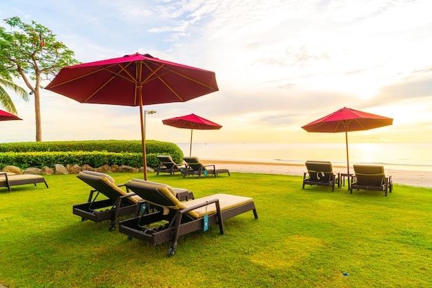 Parapluie avec chaise avec plage de la mer et lever du soleil le matin