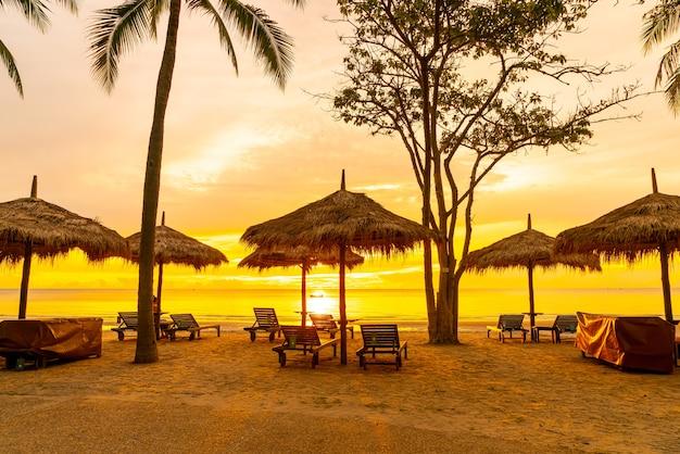 Parapluie et chaise sur la plage tropicale avec lever du soleil le matin