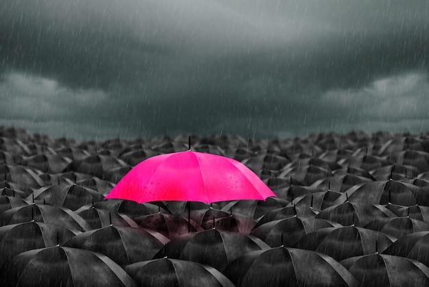 Parapluie coloré dans la masse des parapluies noirs.