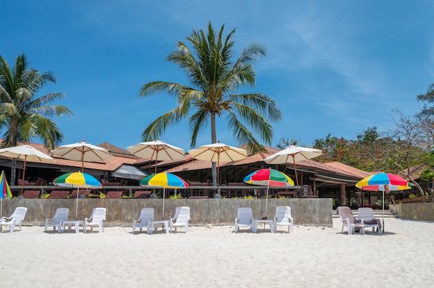 Parapluie coloré avec lit de bronzage sur la plage blanche
