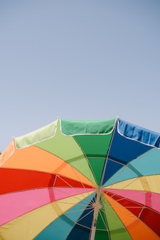 Parapluie de couleur vive ouvert dans le ciel bleu