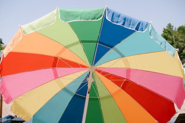 Parapluie de couleur vive ouvert sur une surface de ciel bleu