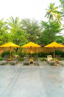 Parapluie et décoration de lit de piscine autour de la piscine de l'hôtel