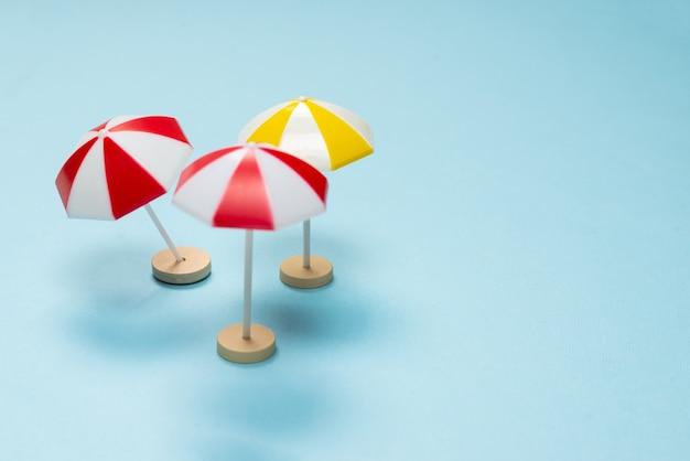 Parapluie jaune et rouge sur fond bleu. espace de copie.