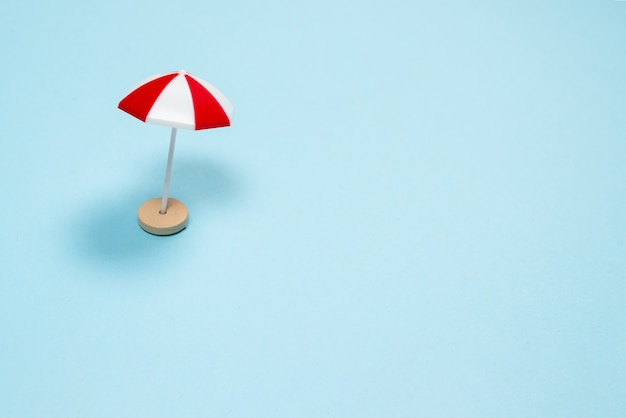 Parapluie rouge sur fond bleu. espace de copie.