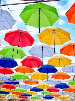 Des parapluies sur le thème de l'automne sont suspendus au-dessus de l'allée du parc. des parapluies colorés suspendus au-dessus des arbres du parc