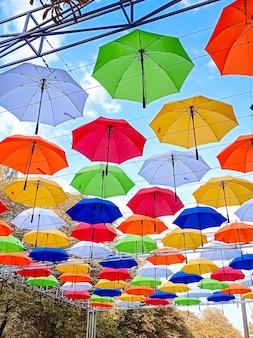 Des parapluies sur le thème de l'automne sont suspendus au-dessus de l'allée du parc