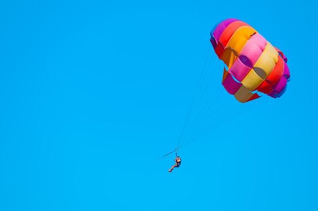 Parasailing sur ciel bleu. espace de copie, activités amusantes de vacances. couple sous parachute suspendu dans les airs