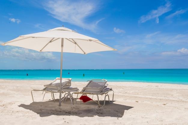 Parasol blanc et chaises longues sur une plage tropicale