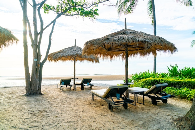 Parasol et chaise autour de la piscine dans un hôtel de villégiature pour les voyages d'agrément et les vacances près de la plage de l'océan au coucher du soleil ou au lever du soleil