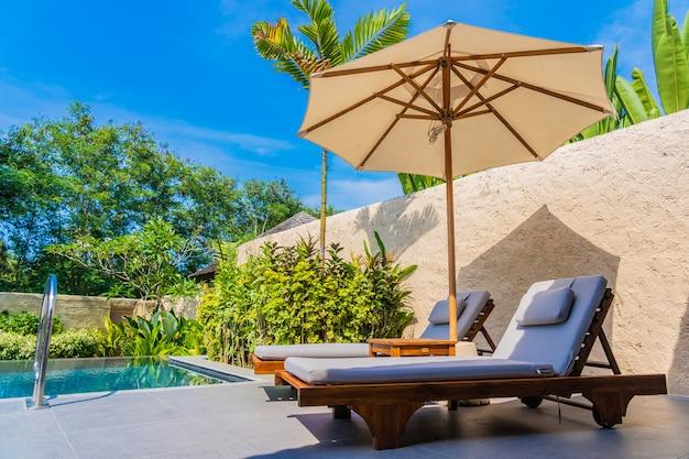 Parasol et chaise autour de la piscine près de la mer, plage de l'océan avec ciel bleu et nuage blanc