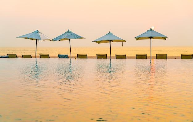Parasol et chaise autour de la piscine avec vue mer