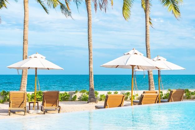 Parasol et chaise longue autour de la piscine extérieure dans un complexe hôtelier avec plage mer océan et cocotier