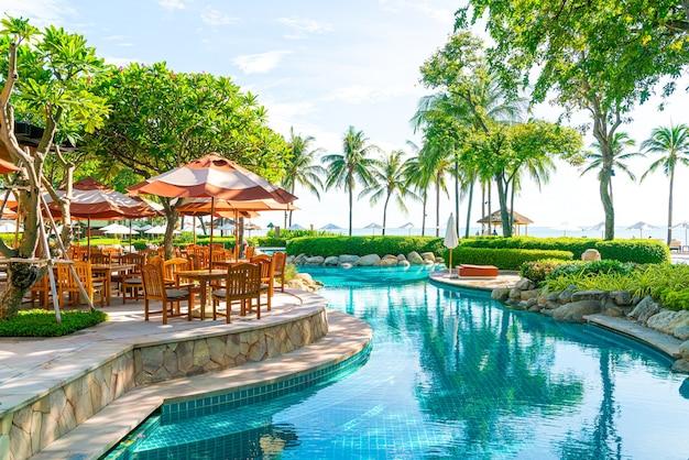 Parasol avec chaise de patio extérieur et table autour de la piscine