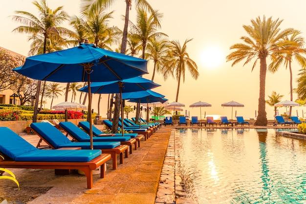Parasol et chaise à la piscine avec des palmiers au lever du soleil