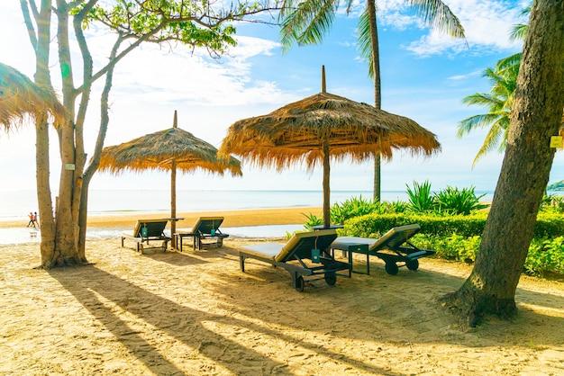 Parasol et chaise de plage avec cocotier et plage de la mer et ciel bleu