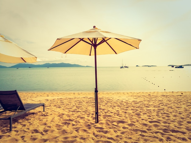 Parasol et chaise sur la plage tropicale, mer et océan au lever du soleil