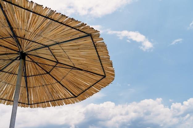Parasol de paille sur fond de ciel bleu