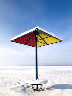 Parasol de plage en métal coloré recouvert d'une couche de neige en hiver par temps ensoleillé, vertical