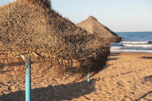 Parasol, plage de sable, mer avec vagues et ciel bleu