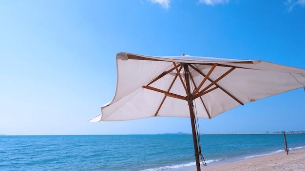 Parasol de plage de texture de tissu blanc et trépied en bois marron avec nuage blanc et ciel bleu clair