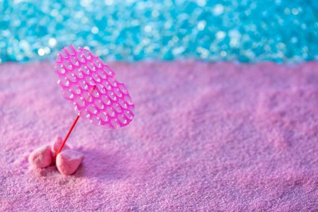Parasol de sable rose de concept de vacances de plage