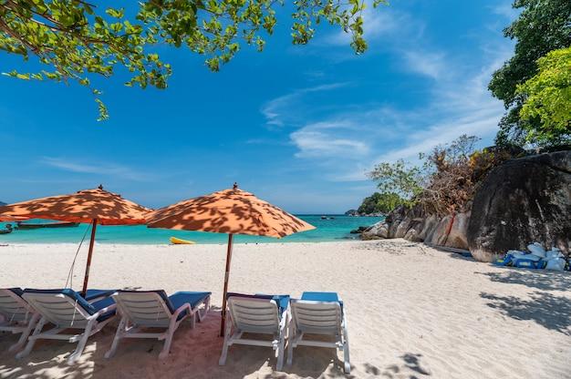 Parasol avec transat sur la plage blanche en mer tropicale