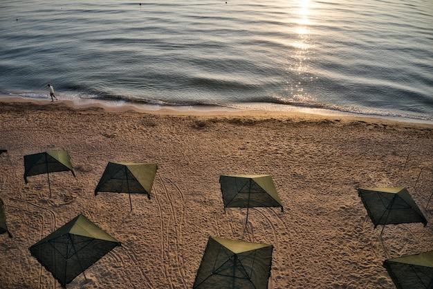 Parasols au lever du soleil et le courant marin nage contre les vagues sur la belle mer