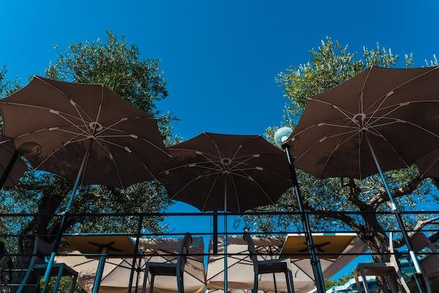 Parasols ouverts pour protéger les touristes qui se reposent à table sur une terrasse du soleil.