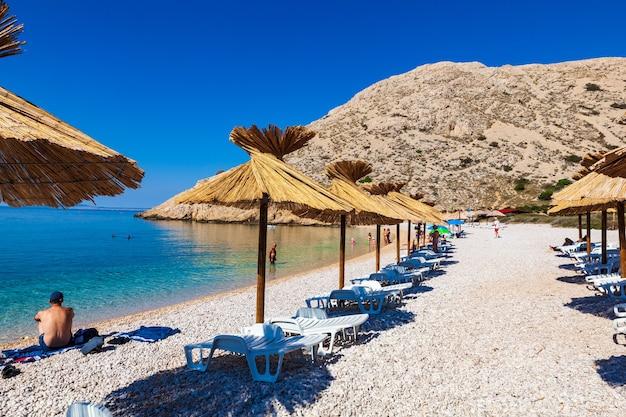 Parasols de paille dans la belle plage d'oprna