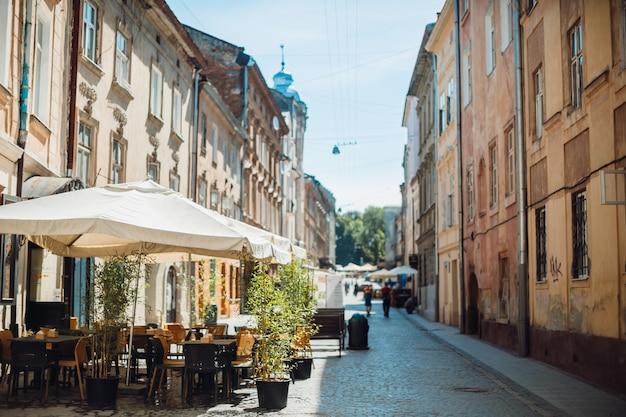 Parasols sur les tables au café sur une vieille rue
