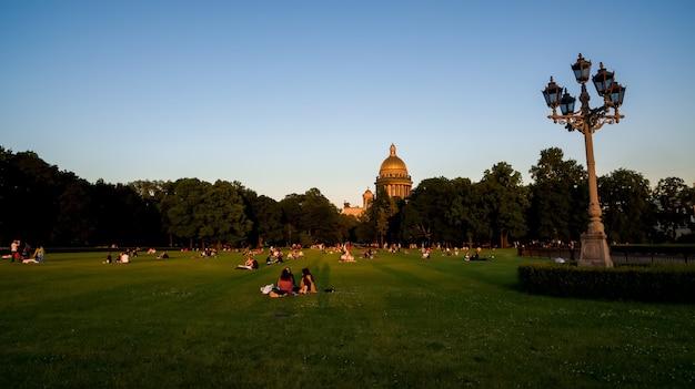 Parc au coucher du soleil à la cathédrale st isaacs et cavalier de bronze