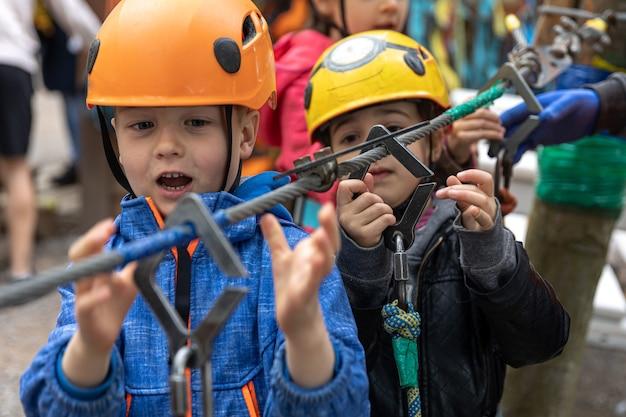 Parc aventure d'escalade sur fil de fer - enfants sur parcours en casque de montagne et équipement de sécurité.