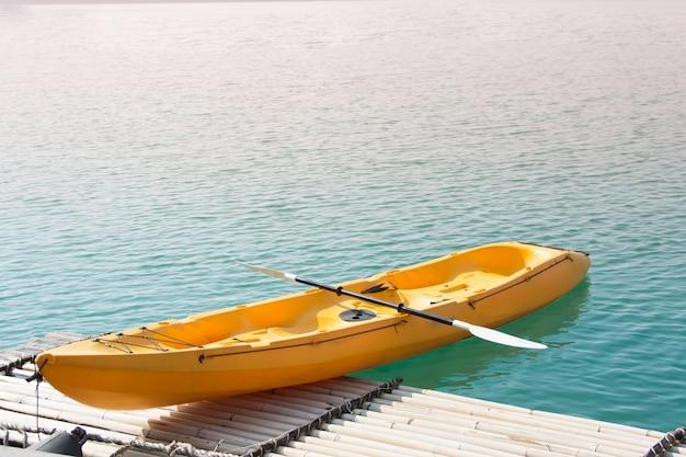 Parc de bateau jaune kayak au quai du lac de la forêt.