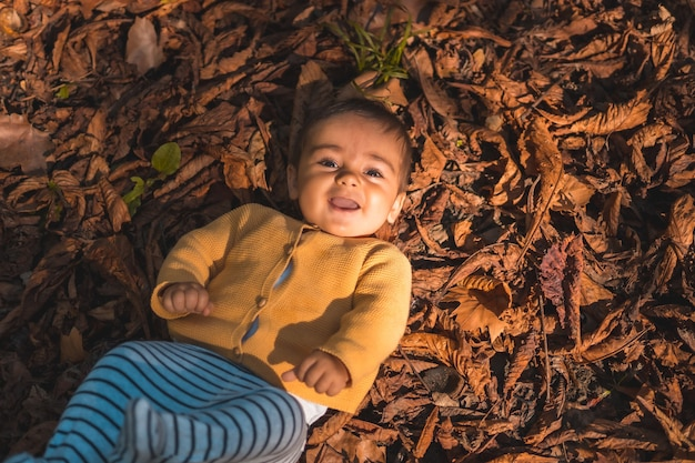 Parc dans un coucher de soleil d'automne, bébé de six mois souriant allongé dans les feuilles des arbres