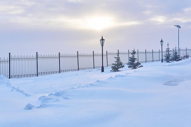 Parc enneigé d'hiver avec une clôture, des lanternes, des sapins et la lumière du soleil qui brille à travers les nuages