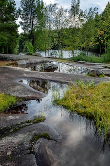 Parc des pétroglyphes de la mer blanche en carélie. grosses pierres, eau et forêt. beau paysage. verticale.