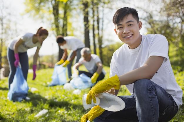 Parc sale. homme volontaire souriant souriant à la caméra lors de la collecte des déchets