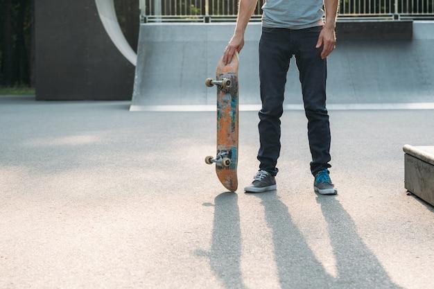 Parc de skate. mode de vie de sports extrêmes. liberté de la culture des jeunes. jambes d'homme avec planche à roulettes.