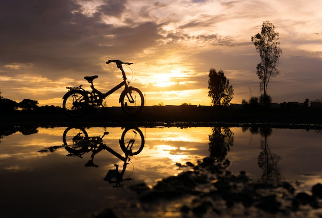 Parc à vélos pliant silhouette au bord de l'eau.